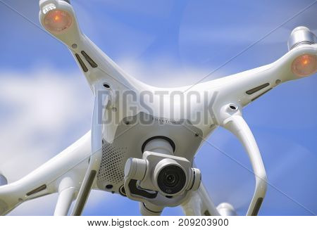 Drone Dji Phantom 4 In Flight. Quadrocopter Against The Blue Sky