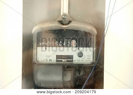 Electric meter closeup behind glass