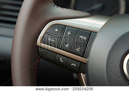 Audio control buttons on the steering wheel of a modern car