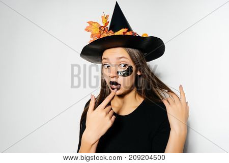 A beautiful witch with long hair scared and looked away. A girl dressed in a black suit and wearing a big witch hat. The Witch was going to a Halloween party.