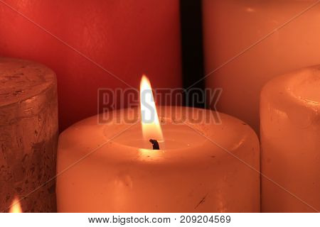 Closeup of a big burning candle ivory color