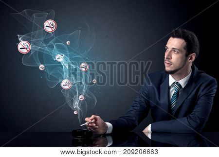 Businessman smoking with floating no smoking signs beside his head.