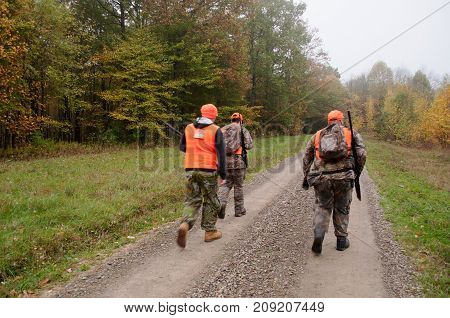 Three hunters walking a dirt road in the woods at the start of the fall hunting season