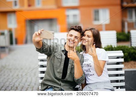 Handsome Young Couple Sitting On The Bench In The Center Of The City And Taking A Selfie With Thumbs