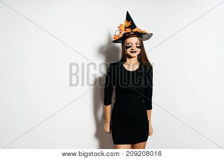 Beautiful young woman in witches hat and costume. Wide Halloween party art desig