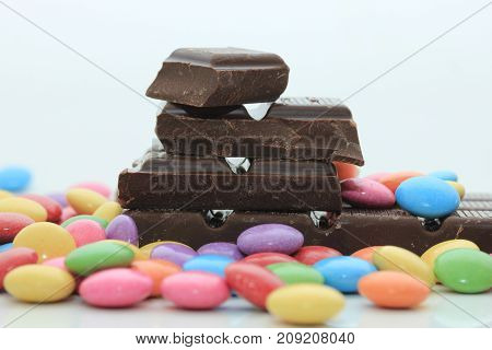 Chocolate filled candies in various bright colors and pieces of a chocolate bar