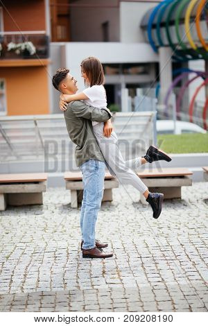 Euphoric Young Couple Meeting And Hugging On The Street. Smiling Couple In Love Standing On The Stre