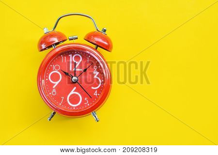 Red alarm clock on yellow background with copy space