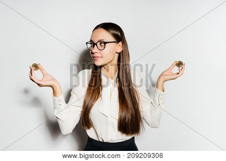 lovely long-haired girl with glasses is holding coins, isolated