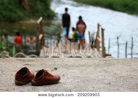Children's shoes lay near the canal with children are enyoy swimming.Thailand.