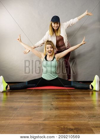Young blonde woman in sportswear stretching body working out with her female trainer. Training at home being fit and healthy.