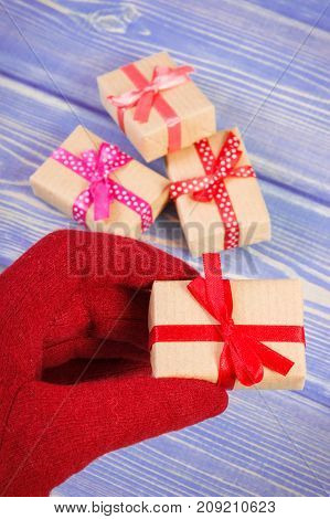 Hand Of Woman In Red Gloves With Gifts For Christmas Or Other Celebration