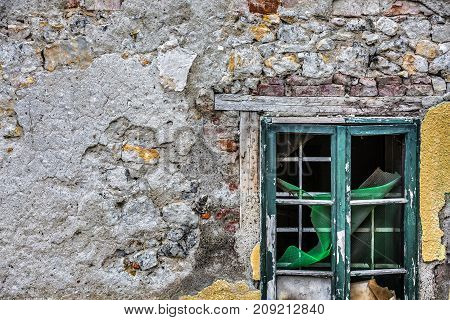 From the window is visible a green mesh and cardboard. The plaster is destroyed brick is seen. Broken window in the gray wall, Valjevo, Serbia.