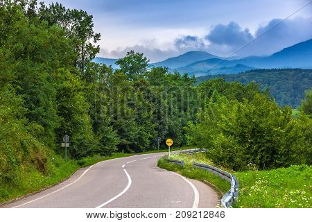 Road with fences and between trees overtaking is allowed - road sign against the background of mountains in the clouds. A winding road to the mountains in Valjevo, Serbia.