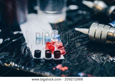 Professional making tattoo in salon. Close-up tattoo machine and tattoo inks . Tattoo equipment