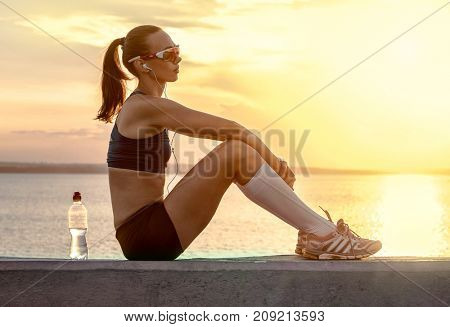 Running woman in sport sunglasses. Female runner with her bottle with water freshness after training outdoor workout on beach. Beautiful fit mixed race Fitness model outdoors.