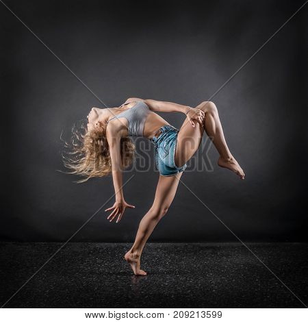 One person,  dancer, woman in dynamic beautiful action figure under lights in background.