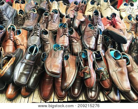 Pile of second hand shoes on shelf at weekend market.
