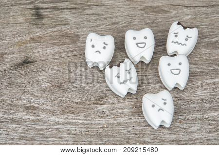 human oral health concept - cute healthy and crying decayed teeth on wooden table