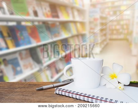 White cup of coffee pen and notepad on wooden table over blur background of book on shelves at bookstore.