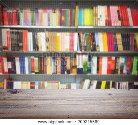 Wooden table for display over abstract blur background of book on shelves at bookstore.