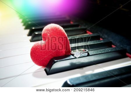 romantic relationship concept : velvet red heart and shiny diamond ring on the piano