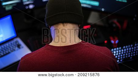 Rear view of man working on computer coding program