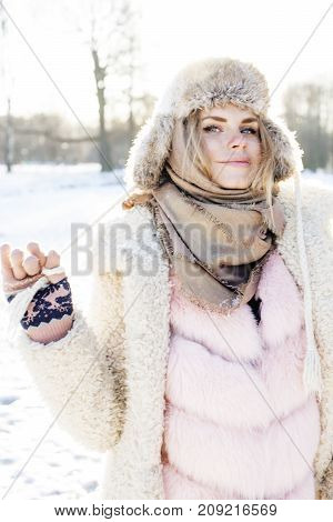 young pretty teenage hipster girl outdoor in winter snow park having fun drinking coffee, warming up happy smiling, lifestyle people concept close up