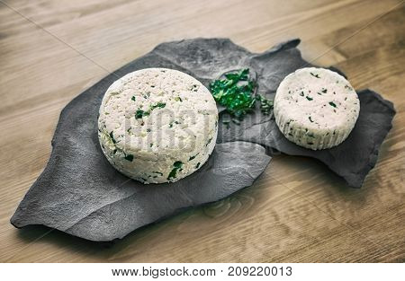 Fresh cheese with herbs on a stone plate