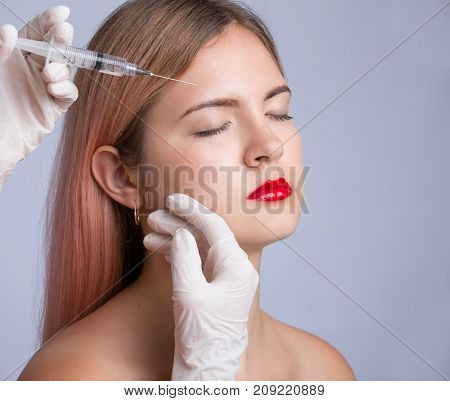 Beautiful young woman with red lips gets cosmetic injection, isolated over greye background. Doctor is making an injection in face. Beauty Treatment.