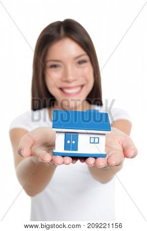 Real estate house market buying home insurance concept. Happy Chinese woman holding small toy home for protection, banking, mortgage, savings, ownership.