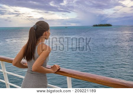 Luxury cruise vacation woman looking at French Polynesia motu island from boat deck at sunset. Elegant tourist relaxing at view of ocean scenery at dusk, relaxing outdoor. Sailing lifestyle holidays.