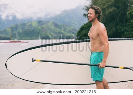 Paddle board water sport man standing with paddleboard on nature beach. Leisure activity in summer outdoor park, happy athlete training SUP paddleboarding.