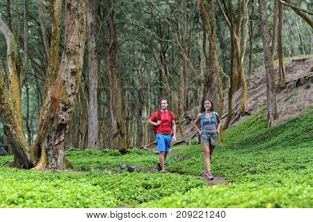 Hiking couple tourists walking together in forest trail path in summer travel vacation destination in Hawaii. Nature rainforest landscape, happy hikers people with backpacks.