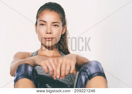 Healthy sport Asian woman portrait. Fitness girl taking a running break post-workout. Chinese athlete relaxing resting at gym. Closeup of face, health and fit concept.