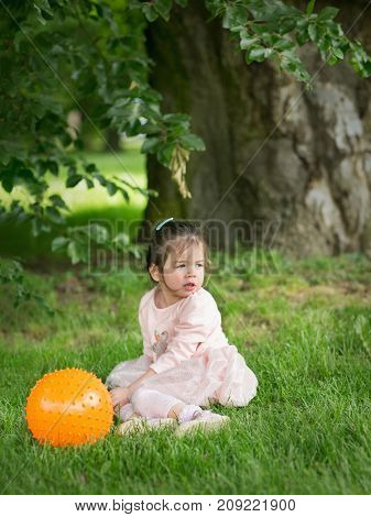 Little girl in a park playing with a balloon