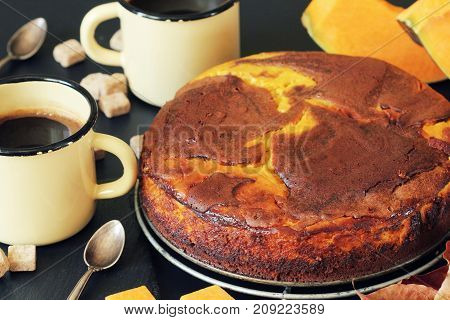 Pumpkin chocolate cake on dark background with fall leaves, top view .