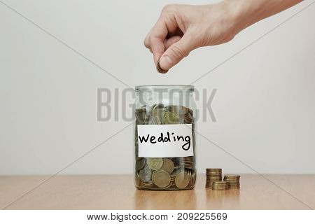 Distribution Of Cash Savings Concept. Hand Puts Coins To The Glass Money Boxes With Inscription 'wed