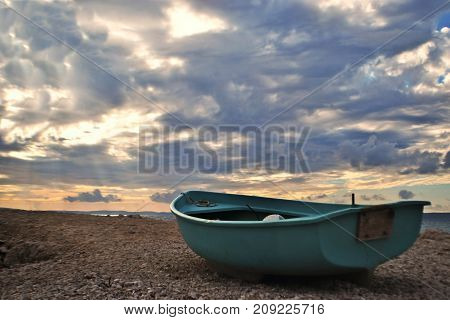 Blue boat at the beach whit beautiful cloudy sky at behind