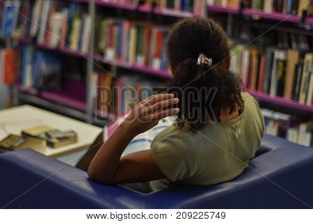 Portrait from behind of young woman sitting at the library and playing whit her hair