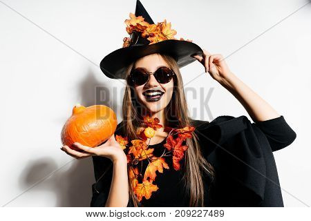 the mad laughing Halloween witch in sunglasses keeps a small pumpkin and holds his big hat. Halloween style, Halloween party