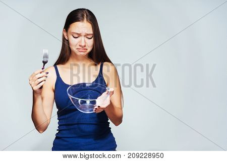 girl looks sad at an empty plate and holds a plug in his hands, isolated on a white background. A hungry girl wants to eat