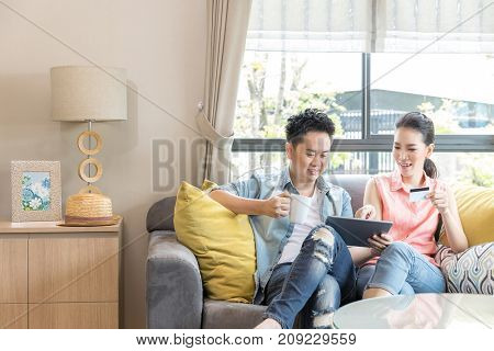 Young Couples using tablet to shopping with credit card in living room of contemporary house for modern lifestyle and e-commerce concept