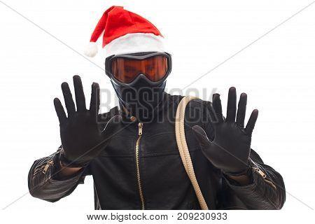 Masked burglar with santa claus cap holding his sack posing on isolated background