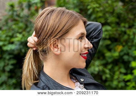 Profile view of a beautiful young woman holding her hair in a ponytail outdoor
