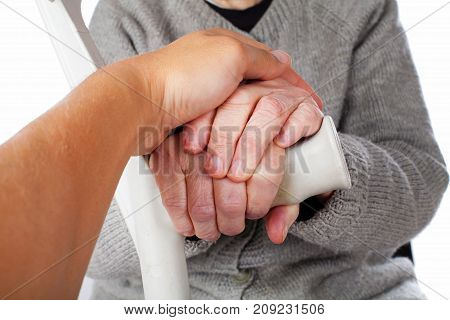 Close up picture elderly disabled woman holding a medical crutch on isolated background