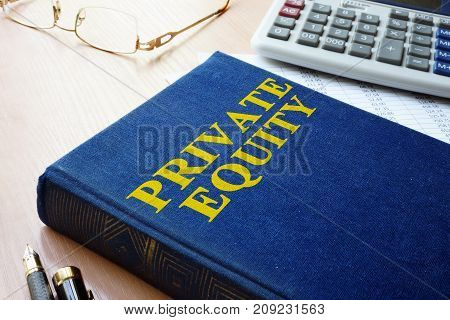 Book with title private equity and calculator.