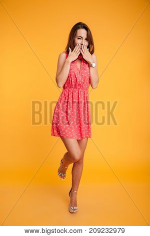 Full length shot of pretty brunette girl in red dress smiling with shy expression, looking at camera, covering her mouth with hands, isolated on yellow background