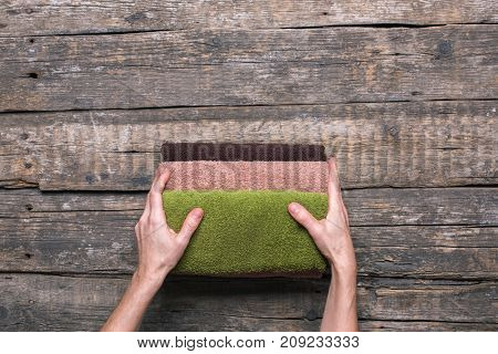 female hands holds stack bath towels colorful cotton terry textile background closeup