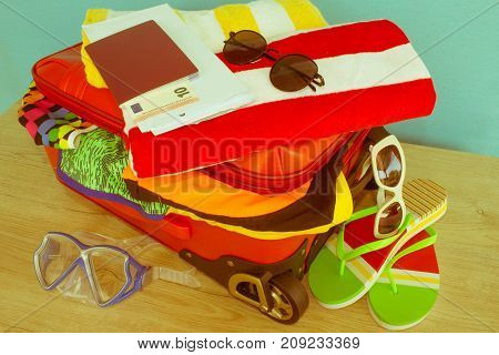 clothes and accessories in red suitcase things prepared for travel. red suitcase with clothing on table - Retro color